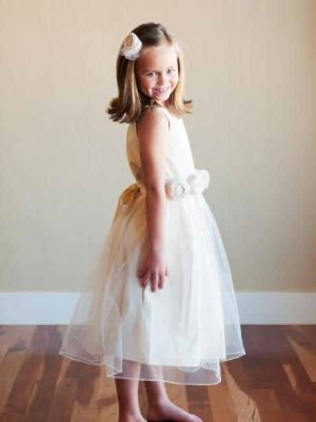 A young girl standing wearing a cream flower girl dress with roses on the sash and a tulle skirt.