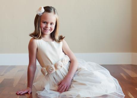 A young bridesmaid reclining wearing a cream flower girl dress with tulle skirt and rosette roses on the belt.