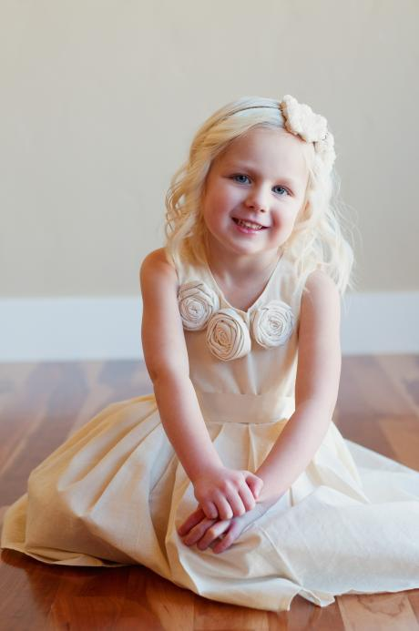 A young girl sitting on a floor wearing an ivory cotton flower girl dress with rosettes around the collar.