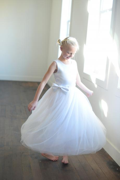 A girl at her first holy communion wearing a satin first communion dress in white with a big bow.