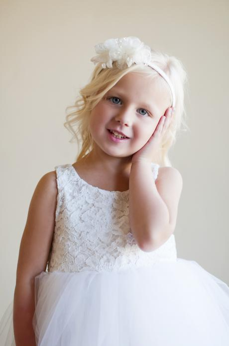 A three year old girl wearing a lace and tulle flower girl dress in white and a flower girl headband.