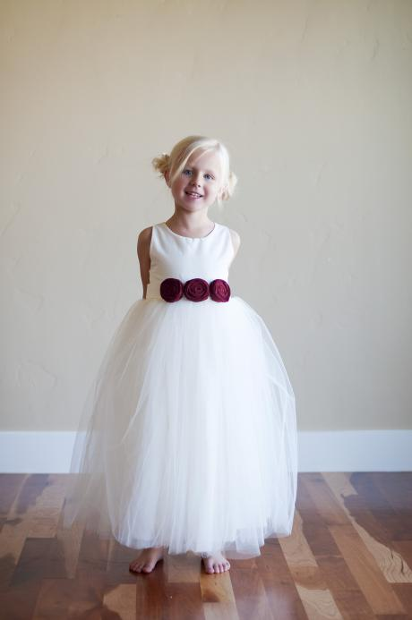 A young girl at a wedding wearing an ivory flower girl dress with three red roses.