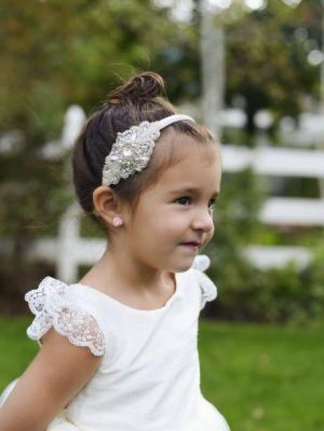 A toddler flower girl wearing a white lace flower girl dress with a tulle skirt
