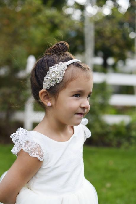 A toddler flower girl in a garden wearing an ivory, lace sleeved flower girl dress and rhinestone headband.