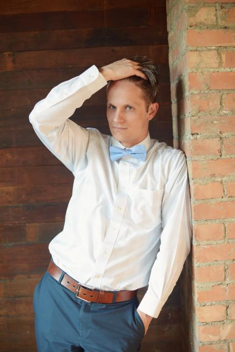 A groom at a wedding leaning on a wall and wearing a light blue bow tie.