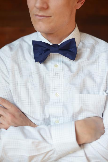 A groom wearing a navy blue silk bowtie and a white shirt