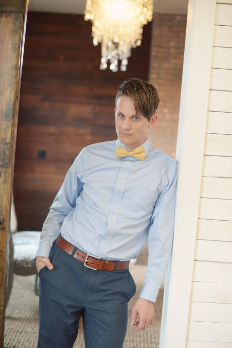 A groom standing by a wooden wall wearing a gold silk custom bow tie.