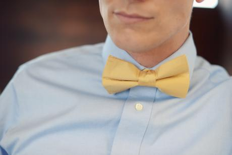 A groom leaning on a wall wearing a gold bow tie and blue shirt at a wedding.