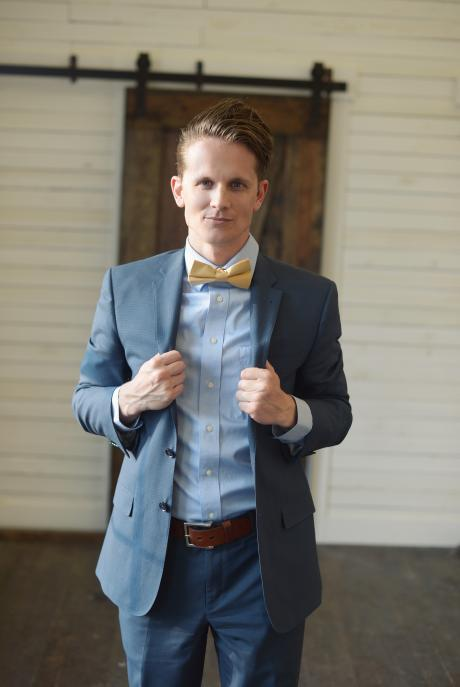 A groom walking towards the bride at a wedding wearing a custom made gold silk bow tie.