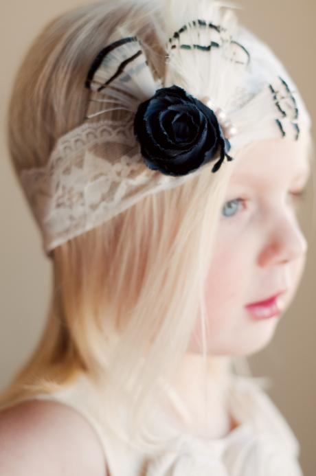 A toddler flower girl wearing an ivory lace flower girl headband with a black flower, pearls and feathers