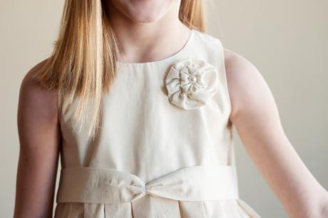 The bodice of a junior bridesmaid dress in ivory cotton with a flower on the shoulder.