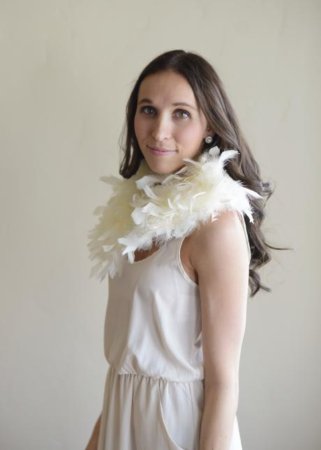 A bridesmaid and a bride wearing an ivory feathered wedding shawl to keep warm.