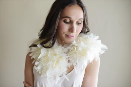 A bride and bridesmaid wearing an ivory feather collar over an ivory wedding dress.