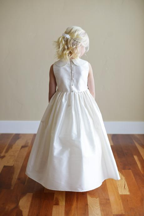 The back of a flower girl wearing a Peter Pan collar dress or junior bridesmaid dress with a big bow and full button back. The dress is handmade to measure in London.