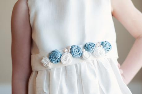 A young flower girl wearing a blue and white flower girl dress with a sash in blue with pretty pearls.
