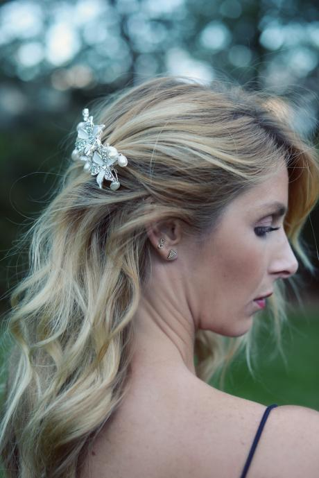 A  white and silver bridal diamante wedding hair comb with pearls placed delicately around two central white flowers.