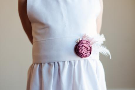 Close up of a white flower girl dress with a pink flower and feather detail.