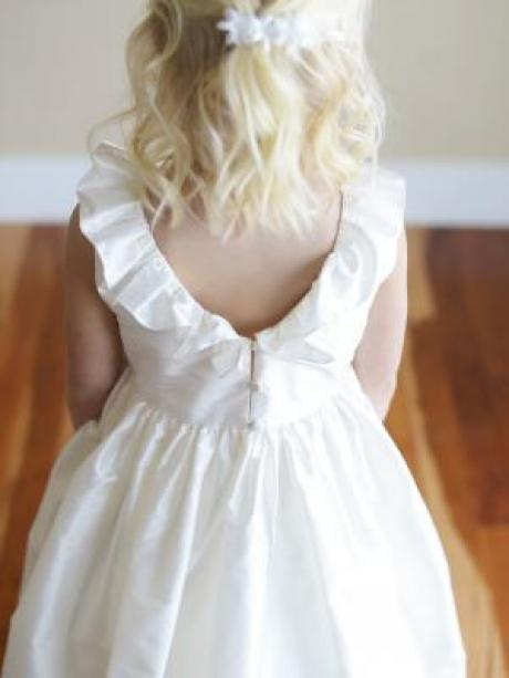 A girl standing and showing the back of a silk flower girl dress with a ruffled V neck collar and full silk skirt.