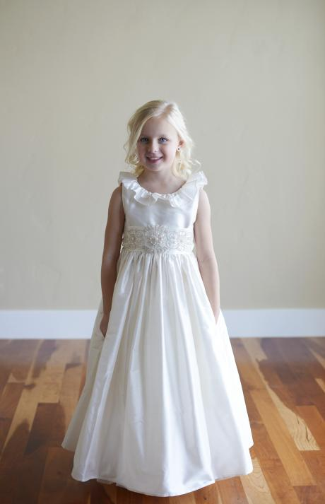 A young flower girl a a wedding wearing an ivory silk floor length dress with a ruffle collar aband ve back. The dress has a wide silk sash with diamante on the front.