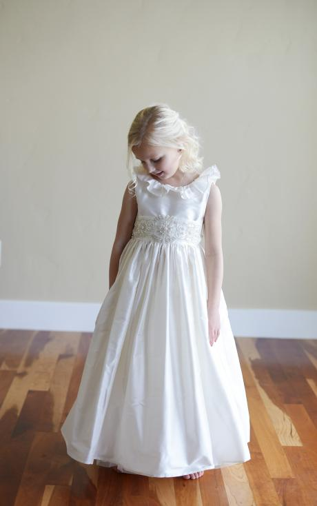 A flower girl standing at a wedding and wearing an ankle length ivory, ankle length flower girl dress with roses on th front.