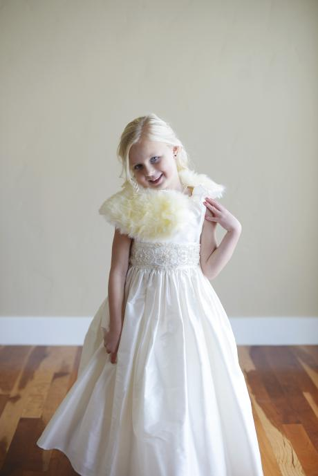A close up of a young girl who is a bridesmaid wearing a  white silk flower girl dress with an ivory sash belt with feather collar. The dress is perfect for winter and summer weddings..