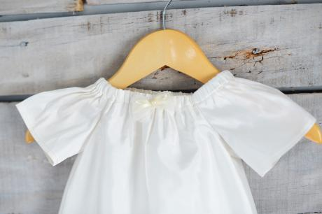 A close up of a made to measure silk christening gown with bow detail a the front.