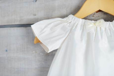 A handmade white silk christening gown with an elasticated neckline and sleeves.