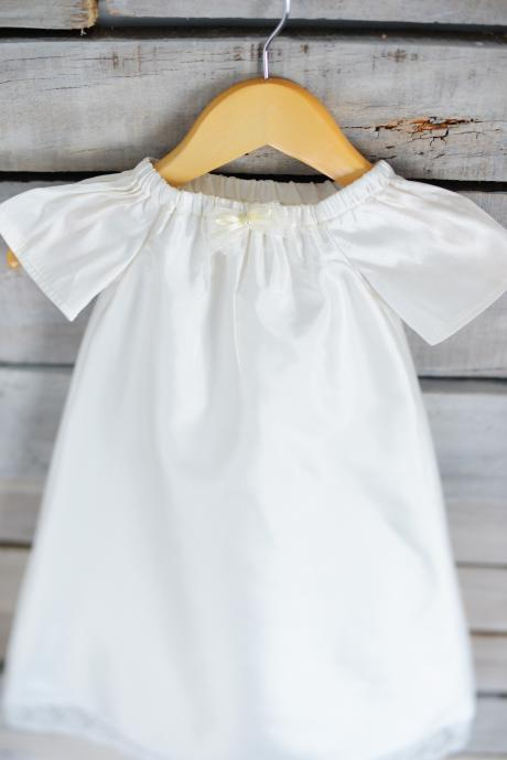A baby at a church wearing a bespoke handmade white silk christening gown with lace trim.