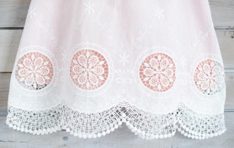 A close up of the bottom of a handmade ivory christening dress with lace circular detail