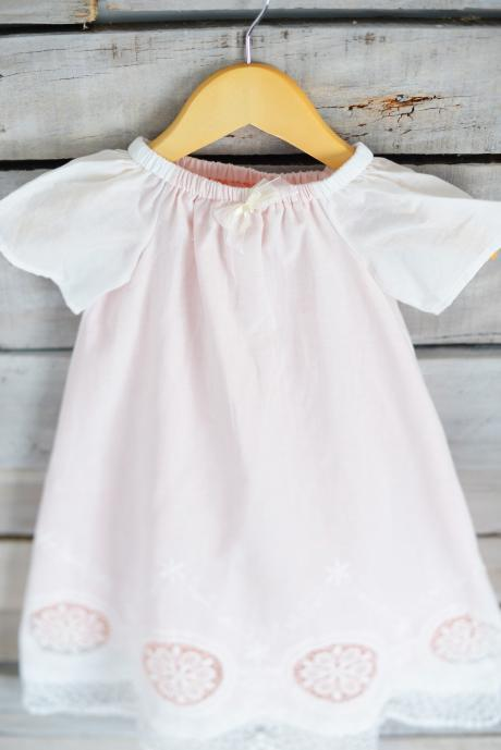 A handmade christening dress in ivory and pink with lace detail and short sleeves