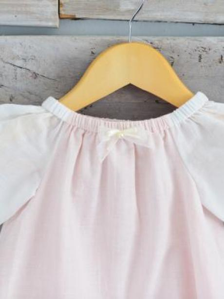 Close up of a pink and ivory christening dress with a small ribbon bow and elasticated neck