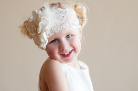A flower girl at a wedding with a bride who are wearing a lace headband with a peony flower and diamante and pearl trim.