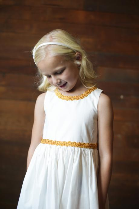 A little flower girl wearing a pearl headband and a cotton flower girl dress with gold braid on the waist and at the neckline.
