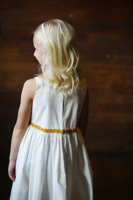 The back view of a young flower girl wearing a cotton dress with gold piping at the neck and around the waist.