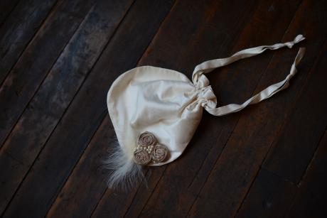 A white and ivory silk draw string first communion purse for flower girls.
