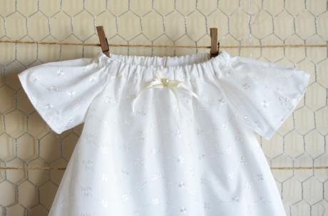 A handmade Embroidery Anglaise christening dress with a ribbon at the neckline