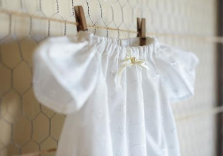 A handmade white christening dress made with embroidery anglaise and has pretty butterfly sleeves and a ribbon at the neckline.