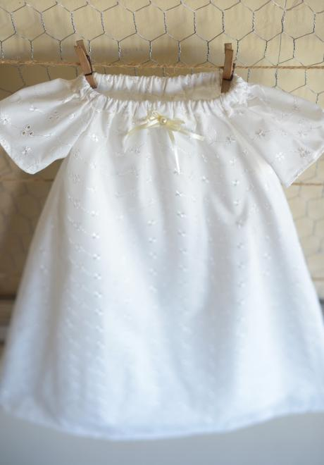 An ivory Embroidery Anglaise Christening Dress with short sleeves and ribbon and pearl detail at the neckline.