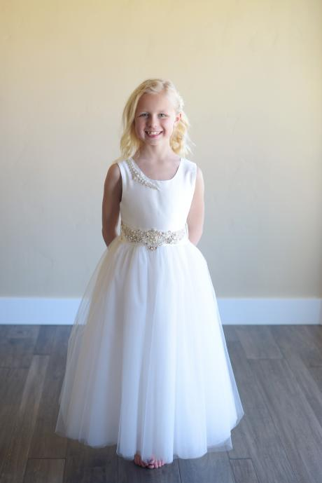 A young girl wearing a handmade, bespoke pure silk communion dress with a tulle skirt and pearls on the shoulder. The dress has a rhinestone belt.