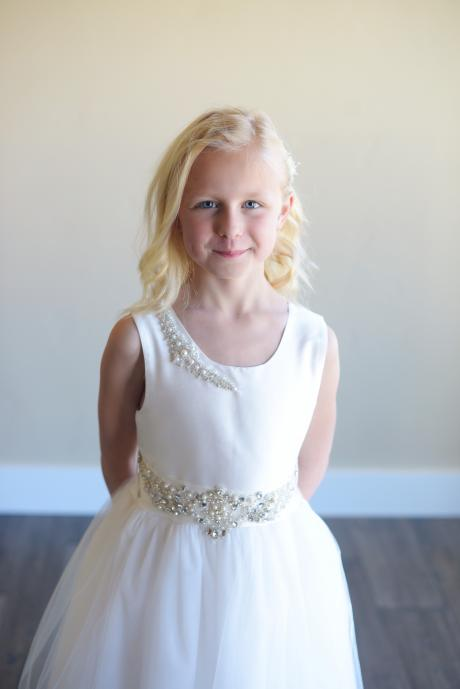 A young girl wearing a white first communion dress with a satin bodice and tulle skirt. Th bodice has a daimante  motif and the sash has pretty rhinestone details