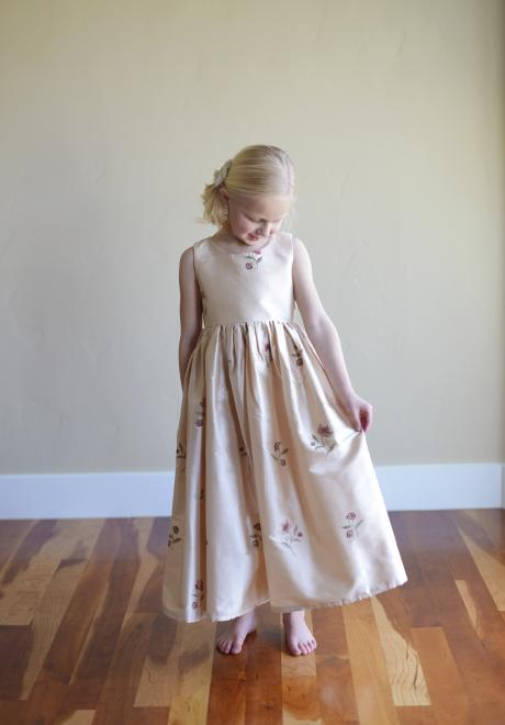 A young flower girl wearing a blush pink embroidered dress with flowers on the skirt and bodice.