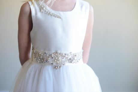 A young girl wearing a white First Communion dress and flower girl dress with a diamanté motif on the belt and the shoulder.