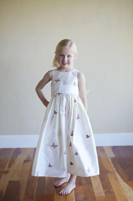 A white, embroidered silk, ankle length flower girl dress with embroidered butterflies.