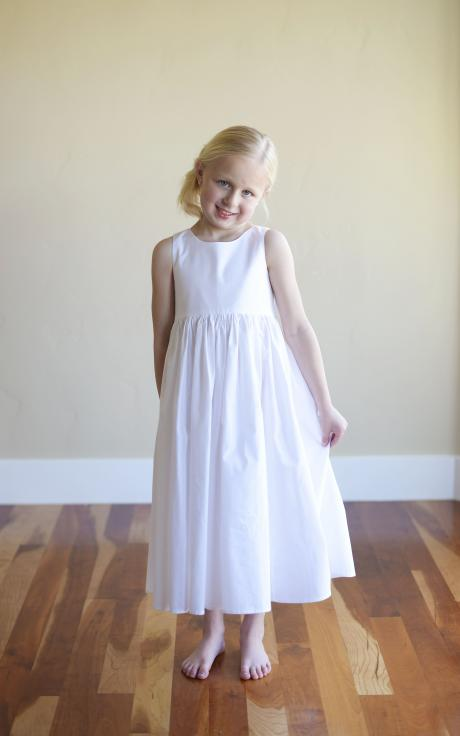 A 6 year old flower girl standing in a room at a wedding wearing a plain white cotton flower girl dress