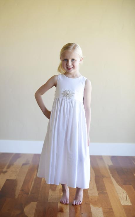 A 6 year old flower girl wearing a white flower girl dress with a star motif on the sash which ties in a  big bow.