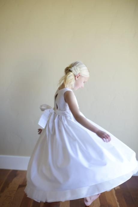 A flower girl wearing a simple white or ivory flower girl dress in cotton with a big bow