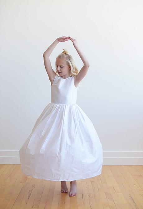 The front of a white silk flower girl dress with a v back and a big bow. The ballerina dress is made in silk and the bow is oversized with large flowers.