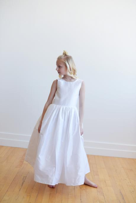 The front of a white silk flower girl dress with a v back and a big bow. The dress is made in silk and the bow is oversized with large flowers.
