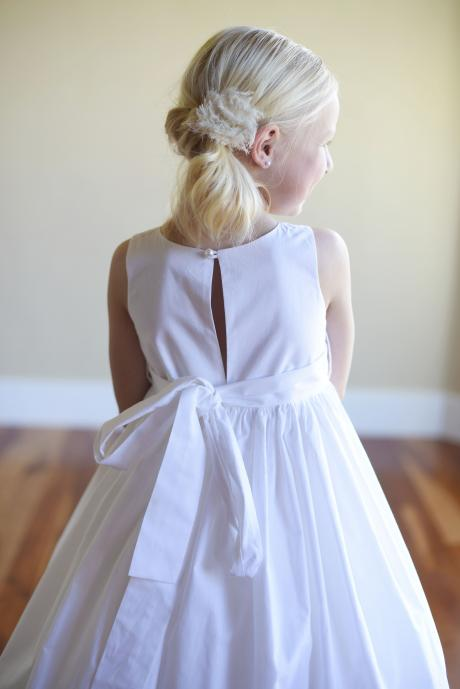 The back of a flower girl dress in white cotton with a star embellishment on a wide belt with a big bow.