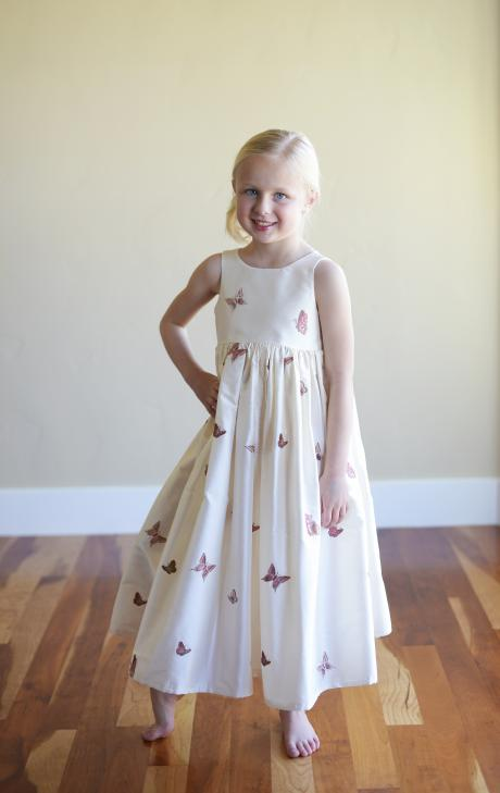 A young flower girl wearing an embroidered ivory silk flower girl dress with butterflies print.